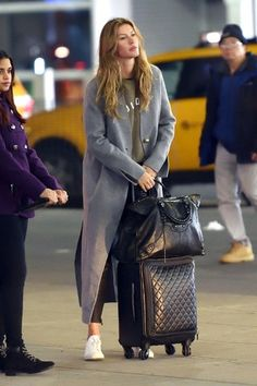 Gisele Bündchen in a gray coat, army green shirt, leggings and white sneakers.