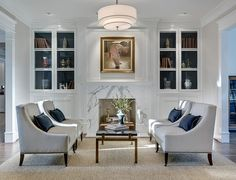 White built-ins, with the backs painted navy blue; Creamy white occasional chairs with navy blue pillows; Drum ceiling light || domiteaux + baggett architects