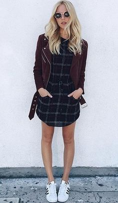 Maroon moto jacket, black and white plaid shift dress, and white and black classic Adidas tennis shoes