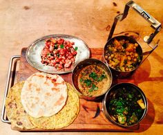 Indian Tiffin box of veggie treats. Red lentil dal; chickpea, onion, aubergine and squash curry; tandoori cauliflower; sag aloo. Served with parathas.
