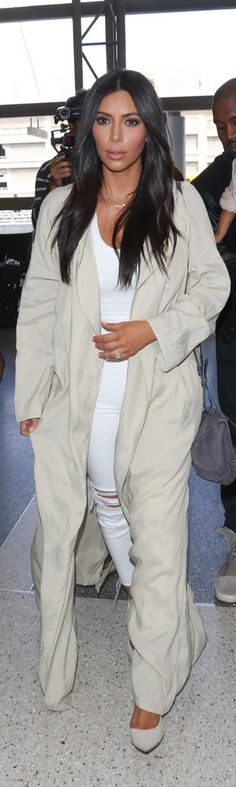 Kim Kardashian wearing a white top and ripped white jeans plus a floor-length off-white coat and high heels