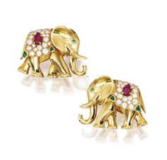 Pair of 18 Karat Gold, Diamond and Colored Stone Earclips, Cartier, Paris, Circa 1960 Designed as elephants accented by numerous round diamonds weighing approximately 1.50 carats, further set with four triangular-shaped emeralds, two rubies carved with foliate motifs, and two round emerald eyes