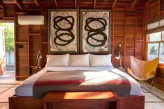 Zen bedroom with artwork over headboard and wood walls and ceilings