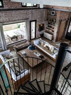Living comedor de una casa de campo con biblioteca rematada por un cajón de madera, sillón sin respaldo en marrón, escalera de hierro negro y grandes ventanales.