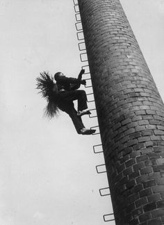 1940: A chimney sweep climbing a chimney. (Photo by Edwina Gnika/Keystone/Getty Images)