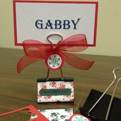"""Cute DIY Christmas place card holder!  Large binder clip, 2"""" x 3 1/8"""" card stock to wrap clip, 12"""" ribbon for bow, 1"""" & 3/4"""" circle punch, 2""""x4"""" name card backed with 2 1/4"""" x 4 1/4"""" card stock"""