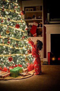 Little girl hanging an ornament on the tree Toni Kami Joyeux Noël Precious Christmas photography idea