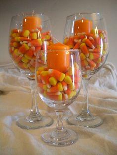 Centros de mesa hechos con caramelos, velas y copas.