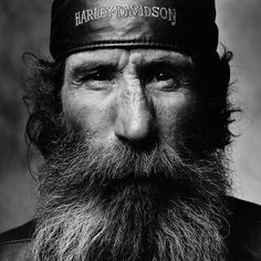 A Harley-Davidson Cap wedged on his head, this man might look threatening from afar, with his long wiry bear and weather-worn features but his eyes tell a different story, softening his harsh appearance. American Bikers by Sandro Miller.    http://dailymail.co.uk/news/article-2217002/The-men-helmets-Black-white-pictures-bikers-new-light.html and/or http://sandrofilm.com/