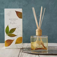 """The warm scents of honey and tobacco blend with notes of almond, patchouli, sandalwood, and amber in this decorative diffuser, hand-crafted in Colorado by Rosy Rings and accented with natural botanicals.- Gingko leaves, larkspur flowers, fragrance oils, glass bottle, wooden cap, 10 reeds- Fragrance will last for 6-9 months- 13 oz.- Handmade in the USA12""""H, 5.25""""W, 2.25""""DDue to U.S. Dept. of Transportation restrictions, this item will ship via UPS Ground and is only available for delivery…"""