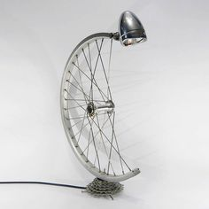 Bicycle Desk Lamp made with a bicycle wheel and gears, with built-in on/off switch. Equipped with bulb fitting and stan.Bespoke Bicycle Desk Lamp made with a bicycle wheel and gears, with built-in on/off switch. Equipped with bulb fitting and stan. Old Bicycle, Bicycle Wheel, Bicycle Art, Bicycle Design, Bicycle Parts Art, Recycled Bike Parts, Recycled Lamp, Recycled Crafts, Unique Desks