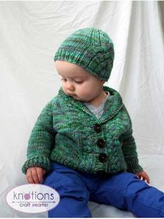 Free knitting pattern for a shawl-collared baby cardigan with buttons up the front, a large cable on the back and small cables flanking the fronts.