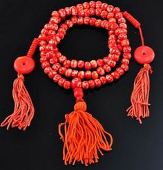 Om Symbol Red Prayer Beads Mala  This mala is made from red yak bone beads. There are 108 beads on this mala. Each bead is 7 mm wide and this mala is 26 inches long. This mala was handmade in Nepal. The Tibetan Buddhist om symbol is written on each bead in the same style as a man-made dZi bead. There are two mala counters on this mala and there are 10 small counting beads on each counter. There is a tassel on the end of the mala.