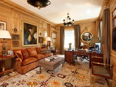 Love this room! Home office with molded walls, large area rug, upholstered sofa, ottoman and chandelier
