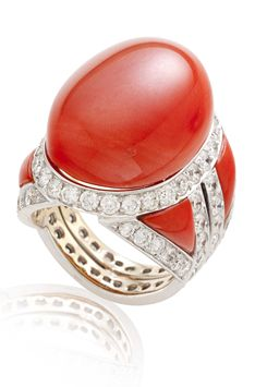 A CORAL AND DIAMOND RING, BY SABBADINI  Set with an oval cabochon coral, within a circular-cut diamond, triangular cabochon coral and 18K white gold mount, ring size 4¼ Signed Sabbadini
