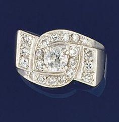 An Art Deco diamond ring  Of geometric panel design, the brilliant-cut diamond centre to single-cut diamond crossover surround and three stone shoulder panels, circa 1930