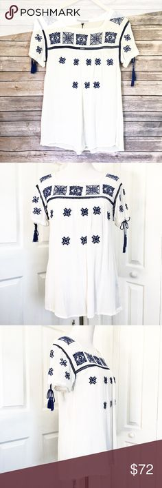 "Romeo & Juliet Couture Blouse Beautiful top by Romeo & Juliet Couture.  Top is white with blue embroidery and peek a boo insert  at the chest.  Arm holes have a drawstring.  Material is 100% rayon.  Measurements laid flat: bust 19"" and length from top of shoulder to hem 27 1/2"".  🚫No Trades🚫No Low Ball Offers🚫 Romeo & Juliet Couture Tops Blouses"
