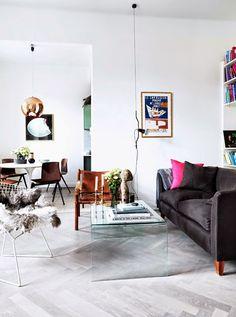 Velvet sofa in living room, Tulip table in dining room, pale herringbone wood floors.