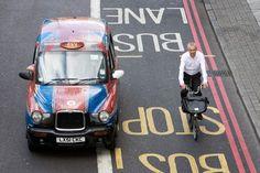 Brompton folding bike beside a London taxi