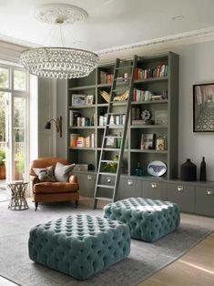 estanterias de madera, salón con sillón de piel y taburetes en capitoné de terciopelo, armario bajo y librería de madera gris, escalera de mano, alfombra, lámpara de araña de cristal
