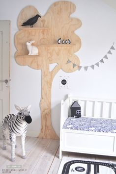 Creative kids room. Wooden tree with shelves. Woodland theme.