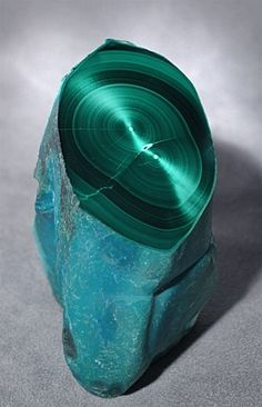 Malachite.    A vivid turquoise blue Chrysocolla exterior has been partially polished to reveal an amazing interior of velvety concentric bands of darker and lighter green chatoyant Malachite. Origin: Congo