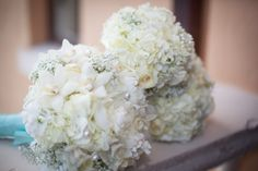 wedding bouquets... all in white, with no greenery at all, and a Tiffany blue ribbon to wrap the stems, along with pearls/rhinestones jewelries for the Bride