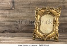 Golden baroque style picture frame on wooden background - stock photo