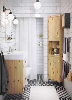 A small white bathroom with wash-basin cabinet and corner cabinet in solid pine.