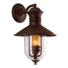 Troy Lighting - 16-Inch Outdoor Wall Light - B9360NB - This attractive outdoor wall light welcomes visitors to the front door with style. The classic lantern-style design fits most any decor, and the sturdy hand-forged cast iron construction features a rich bronze finish. Clear seeded-glass houses an amber-glass cylinder that shelters the bulb, providing the nostalgic aura of an antique gaslight. Takes (1) 60-watt incandescent Flame bulb(s). Bulb(s) sold separately. Wet location rated.
