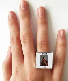 "This is a ring featuring album art of the ""Blonde"" (or Blond) record by Frank Ocean sealed in a silvertone metal setting. The album cover ring measures 3/4"" at the front, is adjustable in size and is"