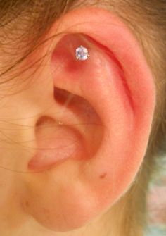 outer conch piercing by Lonnie, body jewelry by Industrial Strength