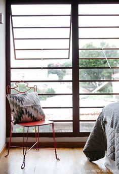 Cadeira vermelha de ferro no quarto de casal dessa casa em SP.