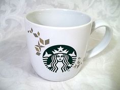 It is delicate white ceramic that has a trail of gold flakes, stars & snowflakes encircling the cup. The back side has a vertical Starbucks logo behind the handle. White Ceramic Mug, with Gold. Starbucks Logo, Starbucks Coffee, Coffee Mugs, Mug Cup, White Ceramics, In This Moment, Tableware, Holiday, Collection