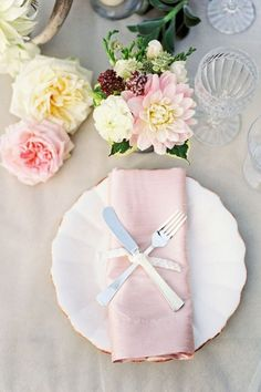 Simple place setting with white charger with gold rim, pale pink napkin and unique setting for silverware. Simple floral with a neutral cloth