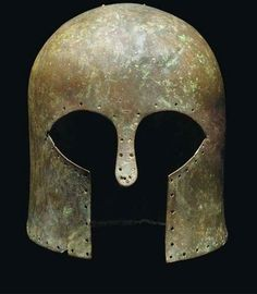Corinthian helmet, late 7th century B.C. Of high domed form, with nose-guard and narrow everted fragmentary flange at rear, pierced with multiple holes around helmet perimeter and twin holes on crown, 22.5 cm high. Private collection, from Christie's auction