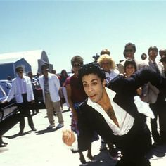 """Prince • 1986 'Parade' Era Photo arriving for the Under The Cherry Moon movie premiere in Sheridan Wyoming """"...stepping off his private jet and onto a slightly soiled 25-foot red carpet, then hurling his black silk sport jacket to the frenzied crowd of 700 that arrived at the airport's one runway to greet him!"""" MTV's Martha Quinn,  Prince managers Alan Leeds and the late Steve Fargnoli can be seen in the background! http://articles.latimes.com/1986-07-03/entertainment/ca-1181_1_warner-bros"""