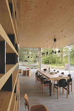The large living room, completely open to the outside, is unified by a wooden ceiling and flooring oxidized rock.