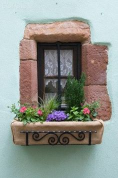 Making the most of what you have is an important part to decorating your house. This small window has been maximised by adding flowers in front of it to make it look pretty.