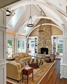 Boston Design Guide~ Beamed ceiling; stone fireplace; built-ins bookcases around the two-story windows; such gorgeous millworker in this open Family Room