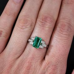 A delicate basket weave in baguette diamonds frame this incredibly high-quality emerald. This fine Colombian emerald is close to flawless to the naked eye, a rare occurrence in emerald, and is richly saturated with a deep, rich green hue. If you have been dreaming of a special emerald to grace your fingers, this may be the one. Of all gemstones, we have found that emeralds are the most difficult to photograph accurately. Thus, these pics don't do this gorgeous, gemmy stone justice. The…