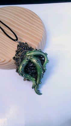 Collar en base de camafeo realizado en resina, con figuras de halloween modeladas totalmente a mano en arcilla polimérica (fimo). Cordón suave (cola de ratón) y cierre anti alérgico en forma de mosquetón. Tentáculos verdes en camafeo dorado, colgante de 5 x 9 cm, 36 cm de largo