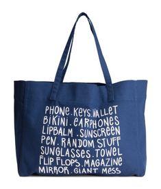 Donkerblauw. Een shopper van katoenen canvas met een print. De tas heeft twee hengsels en een magneetsluiting boven. Ongevoerd. Afmetingen 18x30x40 cm.