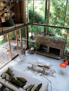 Great living space with walls of glass and a loft. Love how the brick fireplace seems to be freestanding. Mid Century Modern furnishings are nice, too.