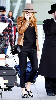 Blake Lively wears all black with a brown leather jacket, loafers, and a tan fedora