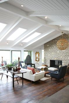 Love everything in this room: floating furniture in center of room + LOVE the skylights in the vaulted ceiling + rafters + natural light + textured wall + round light rixture