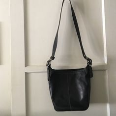 Coach cross body hobo bucket purse Black with beige interior.  Has one zipper inside and one out sider.  Inside has two pouches. Medium size all leather bag!  It zips up closure.   FIRM! Coach Bags Hobos