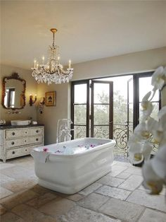 Beautiful Bathroom. Love the Glass doors opening onto the balcony & the chandelier helps set such an elegant mood...