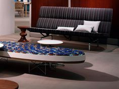 An Eames Sofa Compact with a striped fabric next to an Eames Walnut Stool in a workplace lounge.