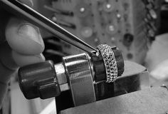 The jeweler is carefully setting the diamonds at our Minneapolis production studio. With all these diamonds the ring is really going to sparkle.